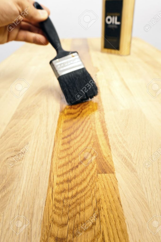 17980832-brushing-a-protective-oil-treatment-onto-a-solid-oak-kitchen-worktop-selective-focus-on-foreground-w-stock-photo
